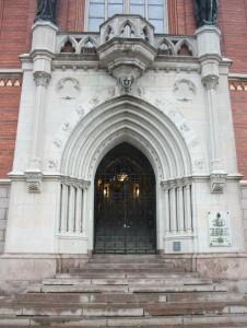 Järngrind i västra entrén. Porten bär formen av en typisk lansettbåge och har arkivolter.